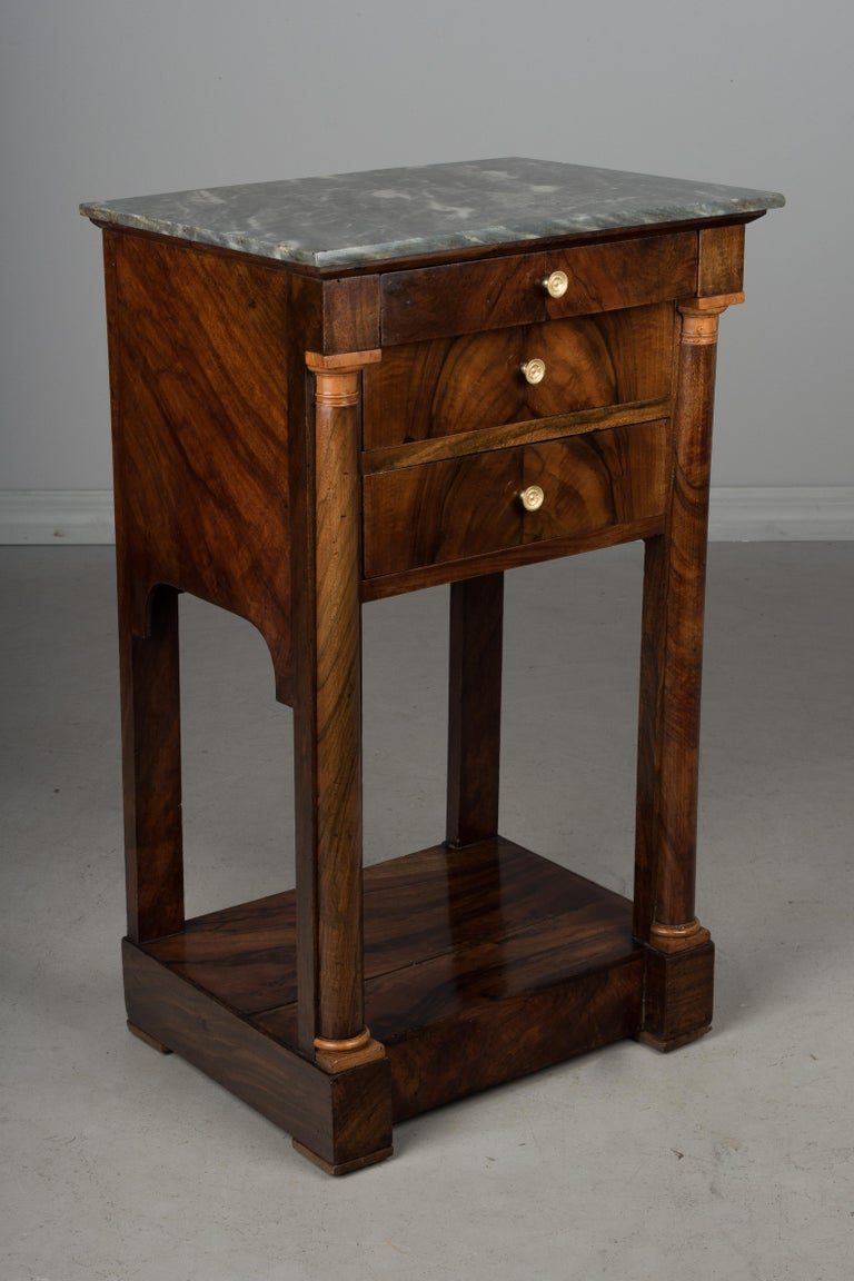 A fine 19th century French Empire marble-top chevet, or side table made of solid walnut with crotch walnut veneer. Pine as a secondary wood. Three dovetailed drawers with replaced brass pulls. Turned wood columns in the front with capitals made from