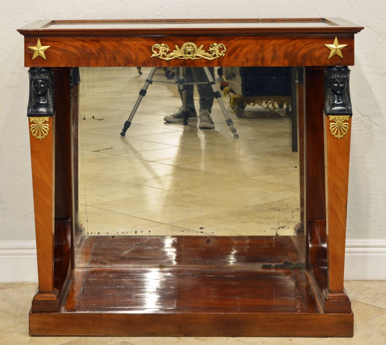 This rare and elegant vitrine console table features a wood framed glass top that opens up to a silk lined vitrine display compartment above a ormolu-mounted frieze resting on two square tapering front legs surmounted by carved ebonized Egyptian