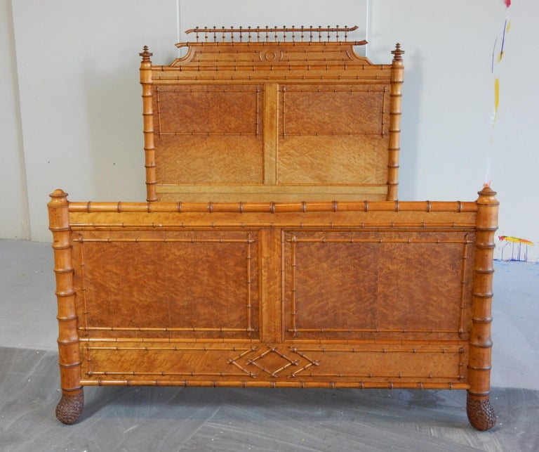Magnificent artisan bed from the mid-19th century aesthetic movement era. Made in France by a master carpenter with faux bamboo detail over gorgeous bird's-eye maple burl veneer. Stylized bamboo legs tapper to a realistic, hand carved bamboo