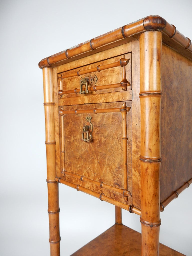 Exceptionally crafted wash stand/table from France, mid-19th century, Aesthetic Movement era. Inset red marble top, a single drawer and a white marble lined cabinet. Faux bamboo stem legs with a realistic, hand carved bamboo