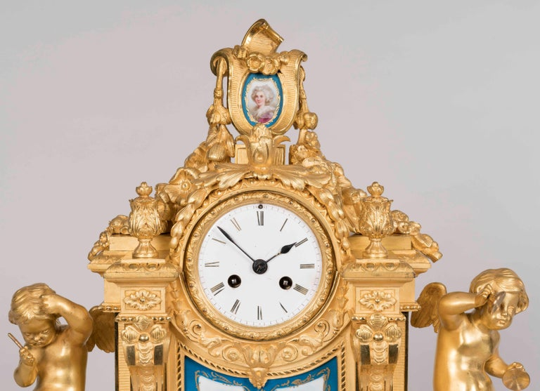 A mantle clock in the Louis XVI taste by Raingo Freres, Paris  Constructed in gilt bronze, and dressed with Bleu Celeste framed porcelain panels, decorated in polychromes, in the 'Sevres' manner, with swags, foliates and putti; rising from toupie