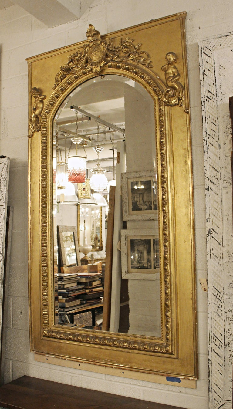 Tall ornate French gilt over mantel mirror with delicate raised cherubs and original beveled glass. This is a 19th century mirror has a rectangular outer frame and center mirror with arched surround. The arched mirror has leafy scroll detail on the