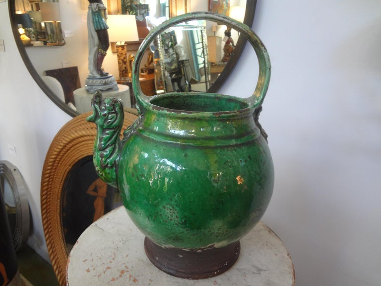 A 19th century French green glazed terracotta pottery vessel or pitcher. This unusual vessel has a dragon spout and mask decoration. This vessel was used for milk or as a vinegar pot (vinaigrier). These vessels were most often from the Southwest