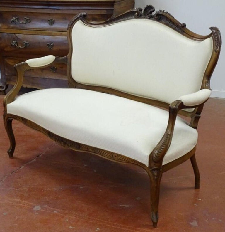 Hand carved walnut canapé in Louis XV style in white silk upholstery. Very elegant legs and beautiful shape. France, circa 1880.