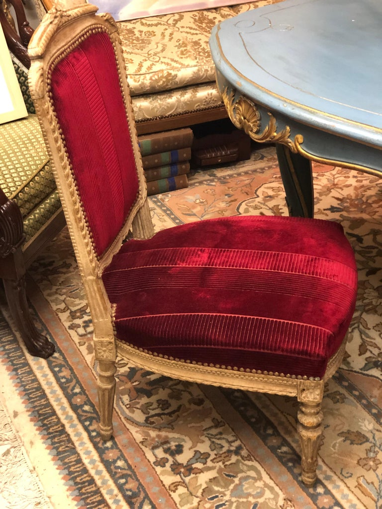 French low seated hand carved chair painted in light beige with elegant decoration in red upholstery and in great condition. Late 19th century.
