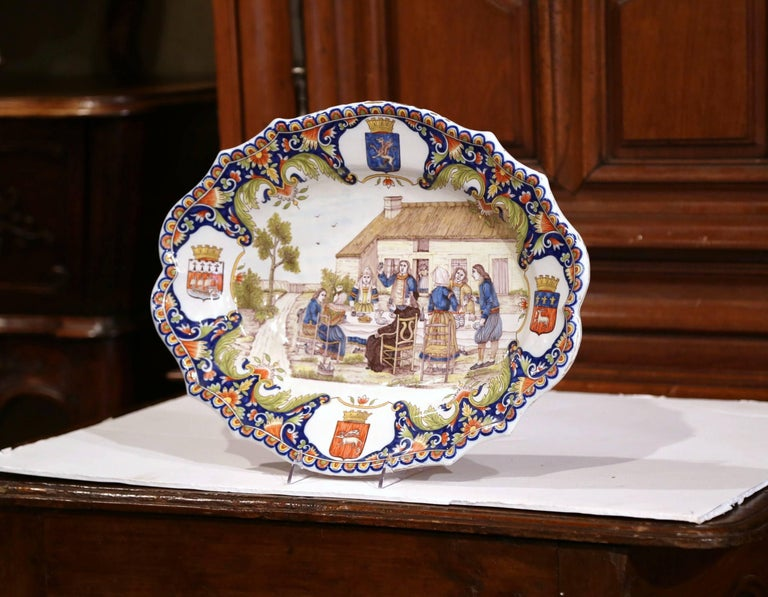 This large ceramic platter was sculpted in Brittany, France, circa 1880. The colorful, antique plate features a hand painted, outdoor banquet scene with Breton people eating, drinking and dressed in traditional clothing. The oval platter is further