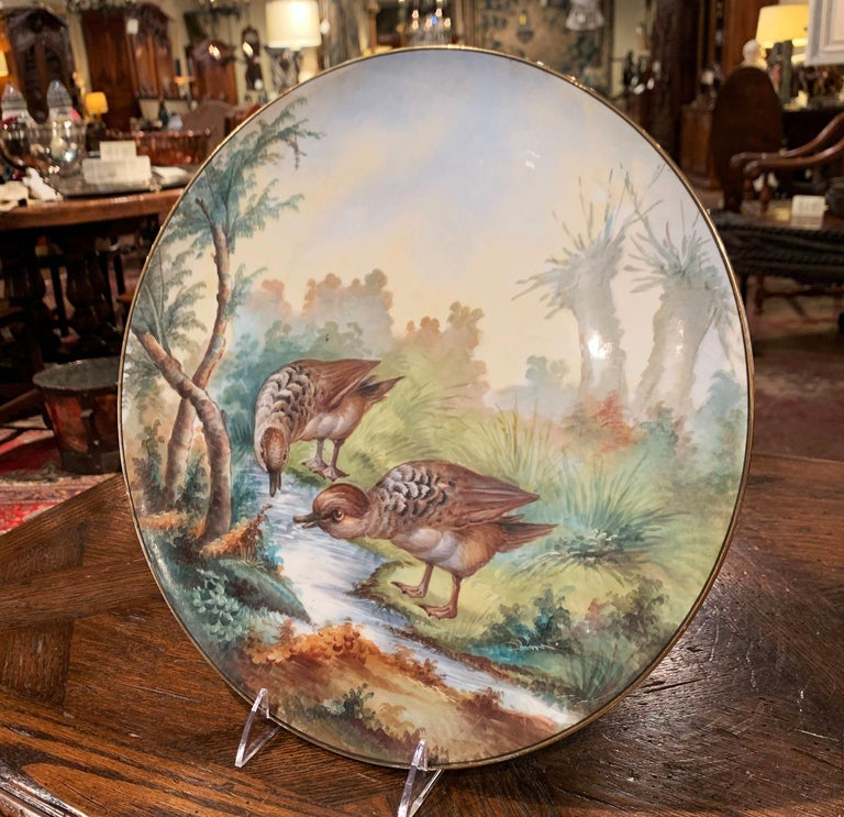 Decorate a wall or a bookcase with this colorful Limoges antique wall platter. Crafted in France circa 1809 and round in shape, the hand painted plate features birds drinking in a river in a luxury landscape; the birds and surrounding scenery are