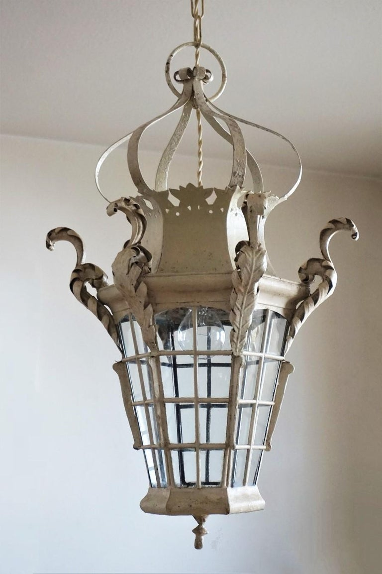 Antique handcrafted wrought iron lantern with original off-white paint, France, mid-19th century. The shaped crown top is leading down to an hexagonal body with glass panels decorated with leaf ornaments, hexagonal glass panel at the bottom. One of