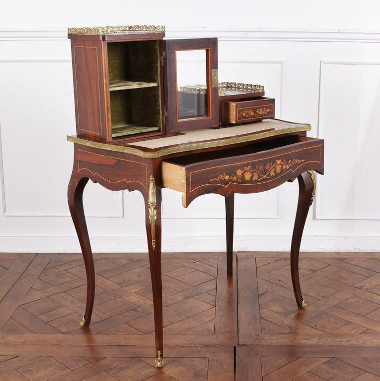 A French 19th century Louis XV style ladies writing desk or 'bonheur du jour' having a drawer beneath the leather writing surface and an upper superstructure with beveled glass cabinet to the left and small upper right-hand drawer. The piece is