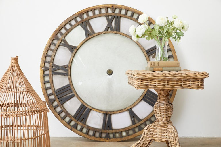 Monumental 19th century French clock face constructed from a 1.25 inch thick iron frame. The large face features Roman numerals and a parcel gilt finish with a beautifully distressed patina. The frame is inlaid with old milk glass. Originally from