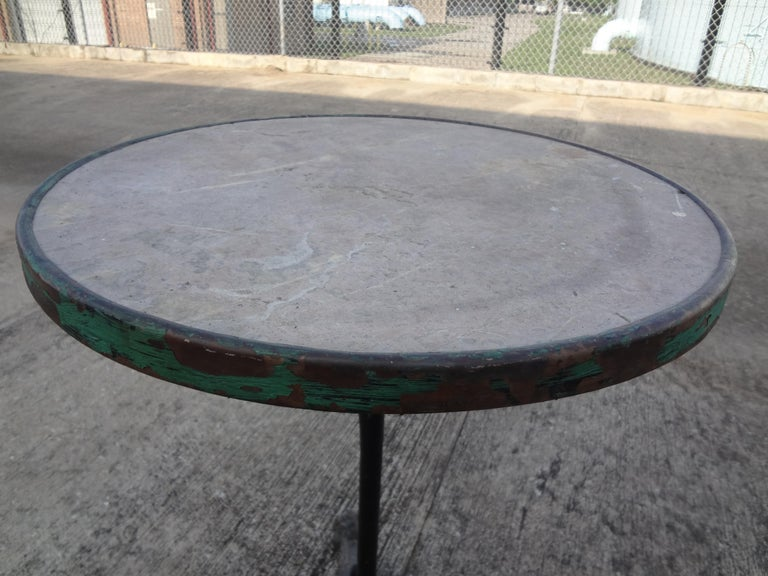 Charming antique French iron tripod bistro or garden table with a stone top. This great little table has a lovely distressed chippy oxidized patina. It would work equally as well indoors as a side table or drinks table or as a garden table.