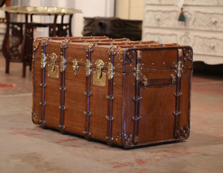 This large Vuitton style trunk would make an elegant coffee or cocktail table! Crafted in Paris circa 1880, the antique luggage is rectangular in shape, and finished on all five sides including the top; it features heavy leather side handles,
