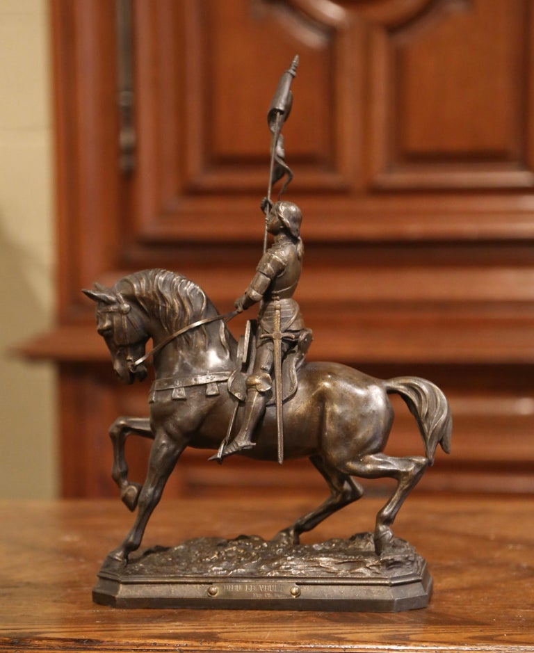 Crafted in France circa 1890, the antique figure depicts Sainte Jeanne d'Arc on her horse waving the victory flag after the battle of Orleans. The sculpture titled