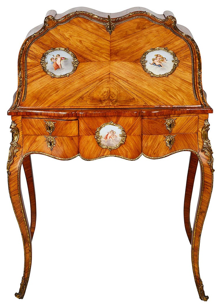 A good quality late 19th century French Kingwood veneered ormolu mounted bureau de dame, in the style of Louis XVI, having quartered veneers to the fall with inset Sevres style porcelain plaques , depicting classical cherubs in the clouds. The fall