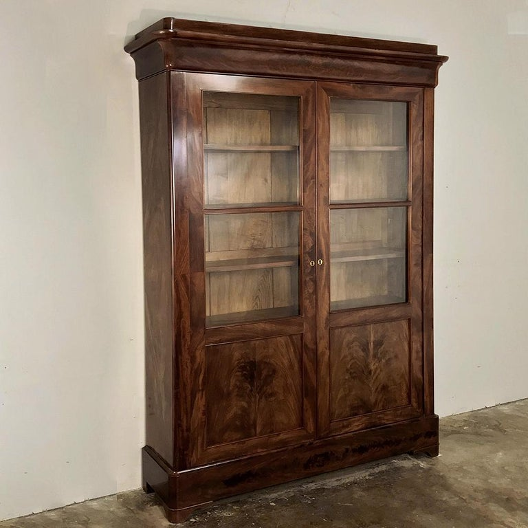 19th century French Louis Philippe mahogany bookcase makes the perfect choice for today's tailored decors! Handcrafted from exotic imported mahogany, it features a generous glazed upper portion with panels below formed by bookmatched flame mahogany
