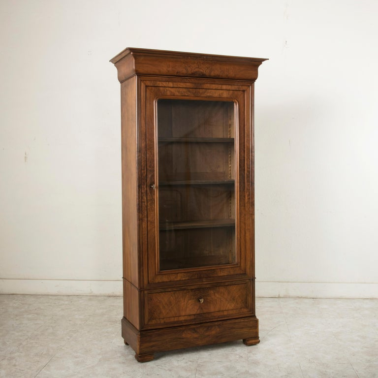 This small scale 19th century Louis Philippe period vitrine or bookcase features a facade of book matched walnut. Its single door is fitted with its original glass and opens up to its cabinet with three adjustable shelves. The shelf fronts are
