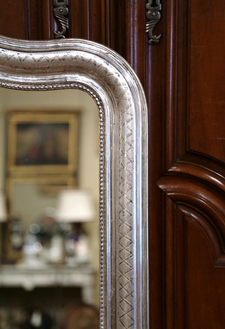 Crafted in the burgundy region of France, circa 1870, the antique wall mirror has traditional, timeless lines with rounded corners and embellished with an arched top. The elegant frame is decorated with a luxurious silver leaf finish, with an