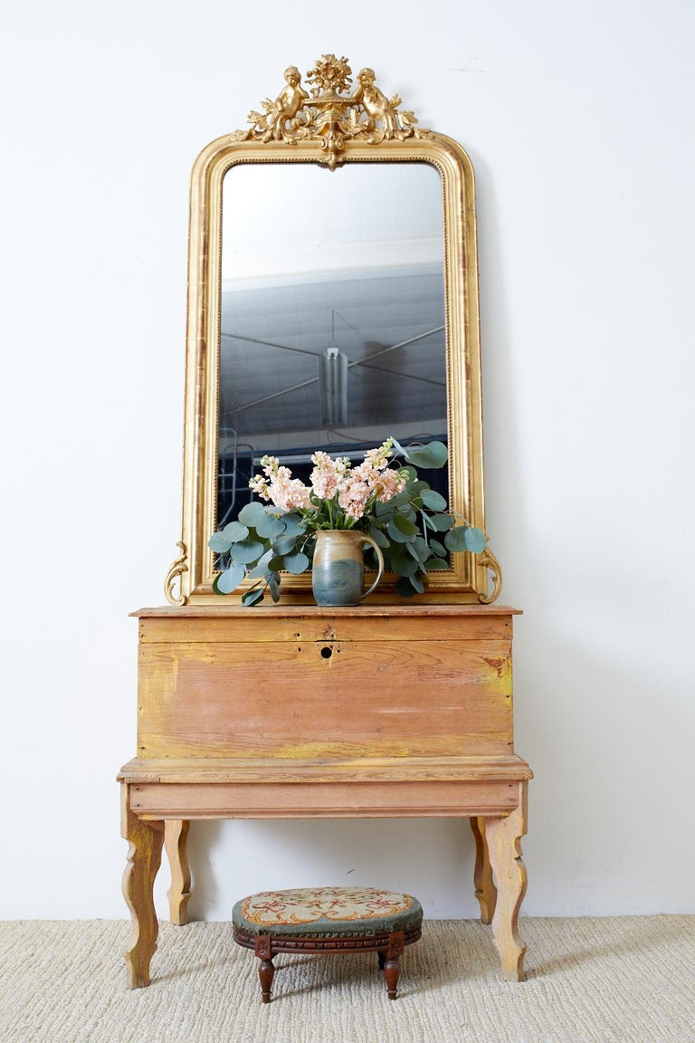 Grand 19th century giltwood mirror made in the French Louis Philippe taste. Features a distinctive gesso crest centered by an urn with floral sprays. Flanked on each side are beautiful cherub figures resting on the urn adorned with acanthus. The