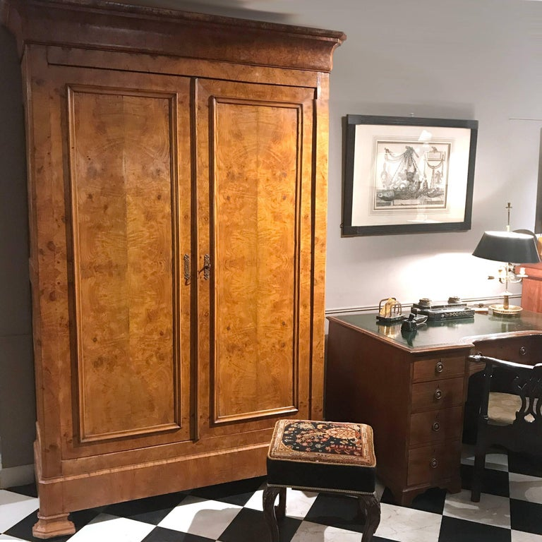 This mid-19th century Louis Philippe-period armoire is distinguished by its architectural feel. The two large panelled doors, with brass escutcheon and key, open to three deep shelves.