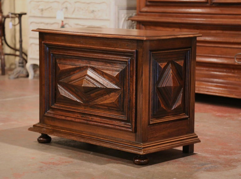 This elegant antique trunk was crafted in Southwest France, circa 1880; made of solid walnut, the chest stands on bun feet over a carved plinth; it features hand carved geometric diamond decor in high relief on the front and both sides. The flat