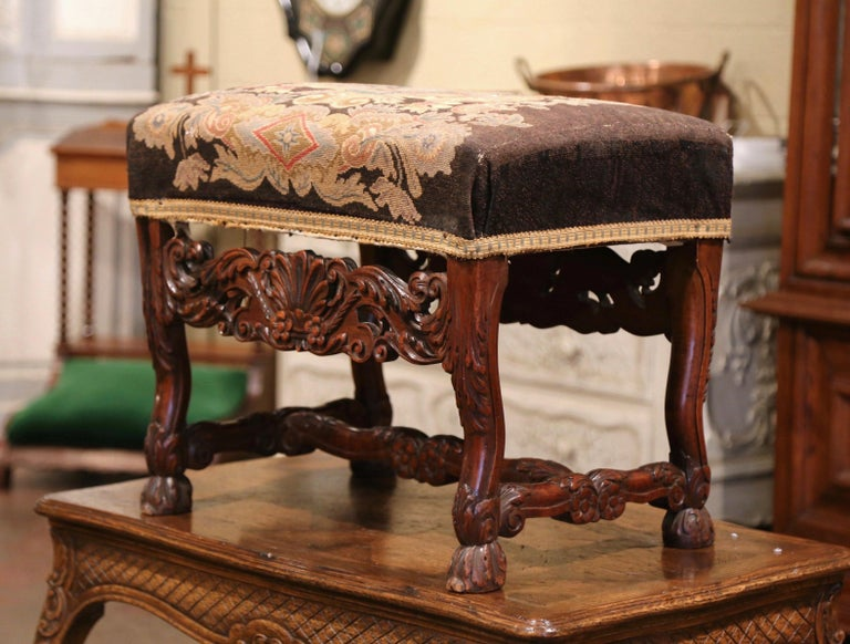 This elegant antique stool was crafted in southwest France circa 1870; rectangular in shape and heavily carved, the stool stands on four scrolled legs decorated with claw feet and acanthus leaves, over a carved scalloped apron embellished with