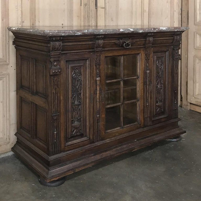 19th century French Louis XIV marble top display buffet was handcrafted from dense, old-growth white oak, and features elaborate architectural detail on the cornerposts with a different variation appearing on the central pilasters. The outer doors