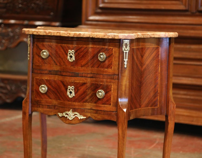 Decorate an living room with this elegant antique chest. Crafted in France circa 1890, the cabinet sits on cabriole legs decorated with bronze caps over the feet. The rosewood commode features two serpentine drawers across the front with inlay and