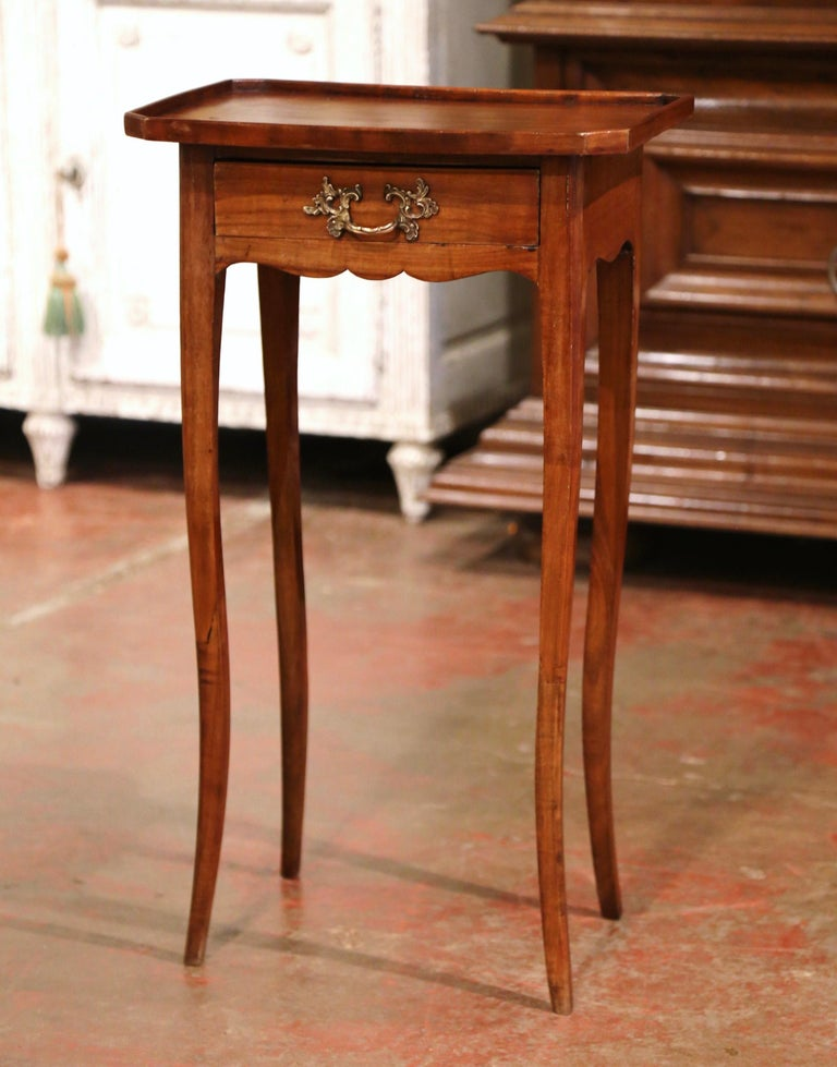 This small fruitwood antique end table would make a beautiful addition next to a sofa in a living room. Crafted in France, circa 1880, the fine side table stands on cabriole legs over a scalloped apron. The petite table is fitted with a small drawer