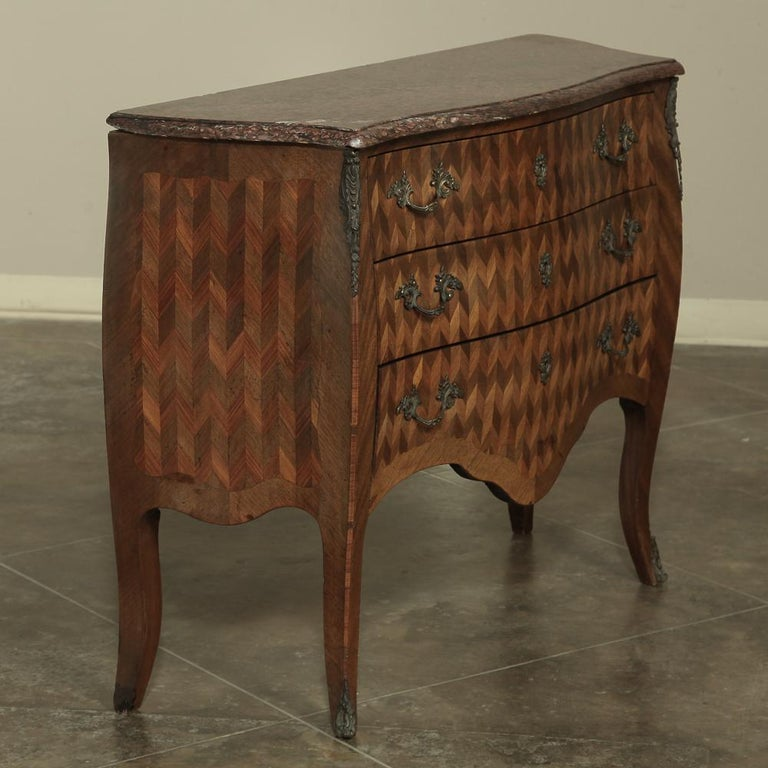 19th century French Louis XV marble-top Marquetry Bombe commode features an intricate inlay of mixed fine and exotic woods creating an art form known as marquetry. Three finely dovetailed drawers display a stunning geometric design repeated on the