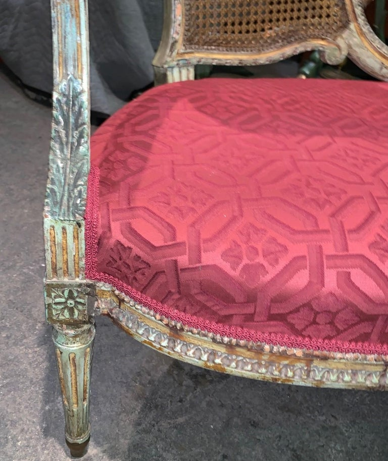 Uniquely styled French Louis XV design painted and caned settee or loveseat. The back superbly carved and ploychromed featuring a quiver of arrows and bow held by a floral motif knotted ribbon. The arms and trim carved with acanthus leaves and