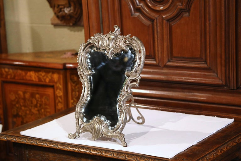 Decorate your master bath counter with this elegant antique dressing mirror. Crafted in France circa 1870, the freestanding table mirror with the original beveled mercury glass, features a centered ornate cartouche, embellished by decorative