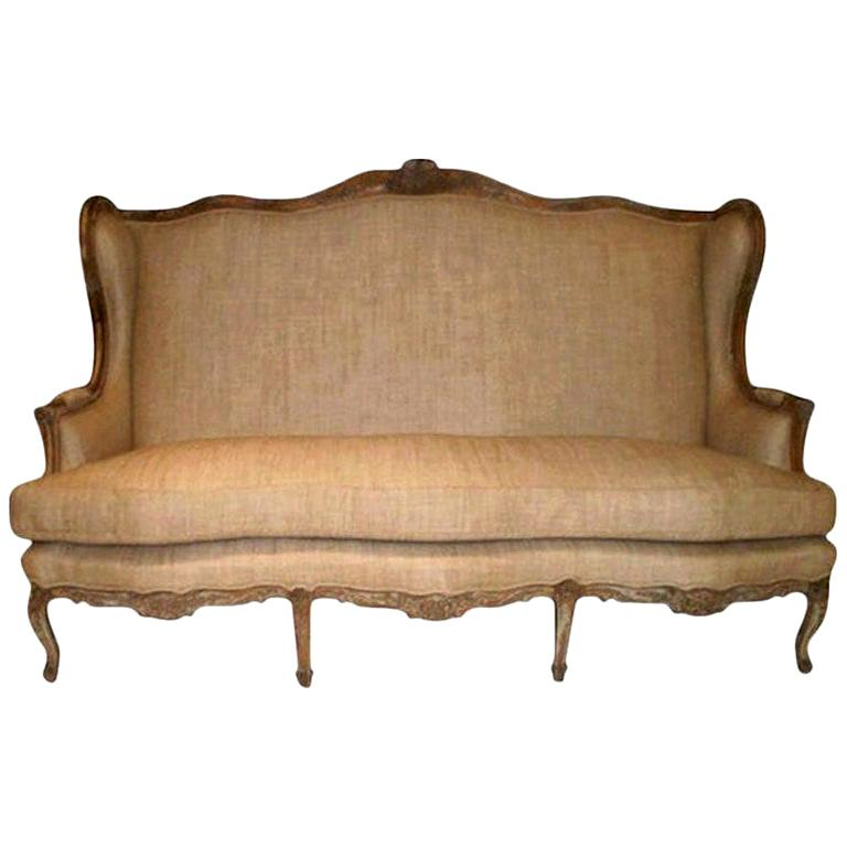 A grand antique French Louis XV style beautifully carved high backed fruitwood canapé or sofa upholstered in oatmeal linen. Underside of cushion has a small tear that has been patched.