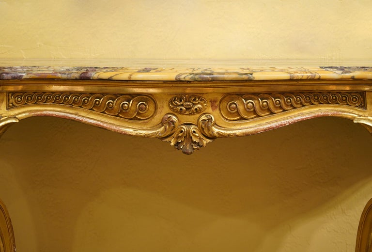 This French Louis XV style console table features a shaped marble top above a serpentine shaped frieze with classical ornaments resting on carved cabriole style legs connected by united stretchers centering a leaf carved finial. A magnificent piece.