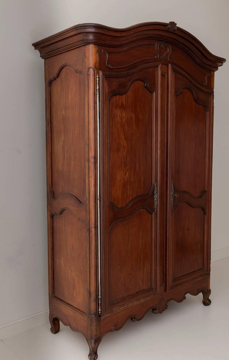 An exceptional early 19th century mahogany wood armoire from the Bordeaux region of France, circa 1810. Arched carved bonnet, two large carved doors, and shaped apron, raised upon cabriole legs. There are three shelves within, the top two are