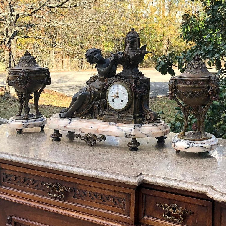19th century French Louis XVI 3-piece mantel clock set after Moreau is a stunningly beautiful set that has remained together for over a century! Set upon luxuriously veined footed marble bases, it consists of a main clock piece and two matching