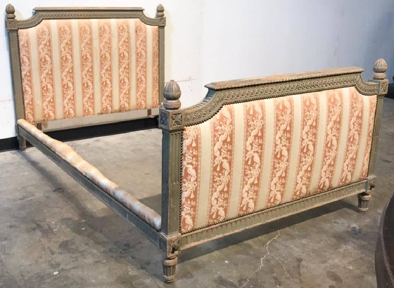 Exceptional 19th century French Louis XVI style bed with finely detailed carving overall of acanthus leaves, flutes, and acorn finials. Beautiful fabric upholstery in a ribbon, tassel, and flower spray motif. Original patina,