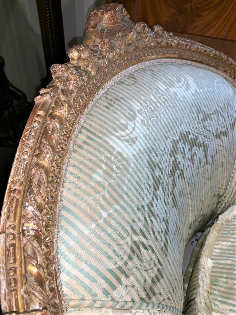 Impressive 19th French Louis XVI style chaise lounge or daybed crafted of carved giltwood. Elegant lines and nicely aged gold patina. Upholstered in silk with tear on the front cushion, (see photos),  circa 1870.