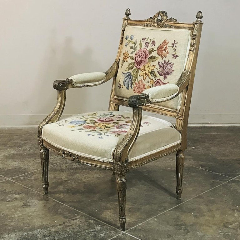 19th century French Louis XVI gilded armchair features fabulous hand carved magnificence on the entire frame accentuated by the patinaed gold finish. Motifs include the classically inspired laurel wreath, pineapple finials, foliate sprays and