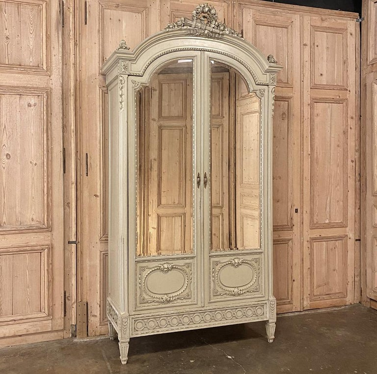 19th century French Louis XVI painted armoire represents the epitome of Parisienne elegance! Handcrafted by expert artisans using time-honored techniques, it exhibits the essence of the classical style, from the boldly arched crown above to the