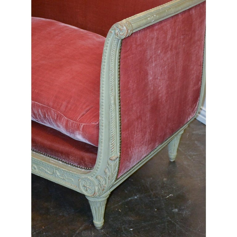 Elegant and stylish 19th century French Louis XVI style sofa with a greyish painted finish, serpentine shaped crest, and lightly contoured arms. Hand-carved overall with stylized flower petals and acanthus leaves. The upholstery accented with brass
