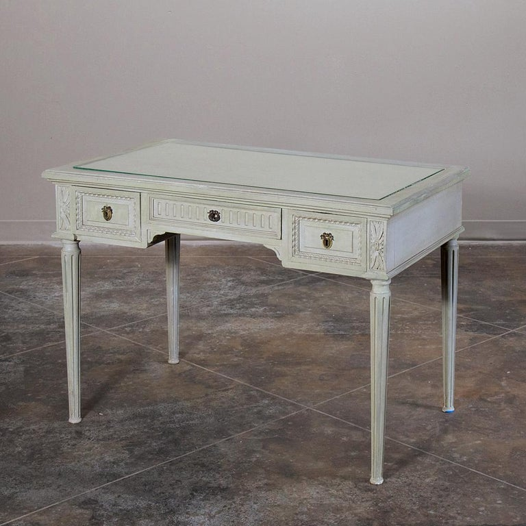 19th century French Louis XVI painted vanity, writing table can perform multiple tasks in style, with a tier of drawers under the fabric & glass top for functionality, and hand carved egg & dart, fluting and acanthus rosettes for decoration, all
