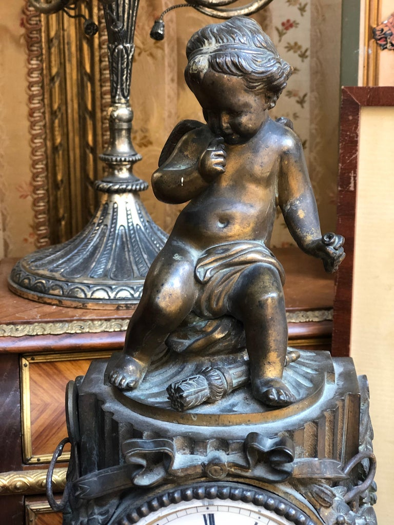 19th century French antique bronze desk or mantel clock dated circa 1870. The clock stands on curved base and features a carved sculpture of a seating cupid. The intricate clock mechanism has been cleaned and checked and is in wonderful working