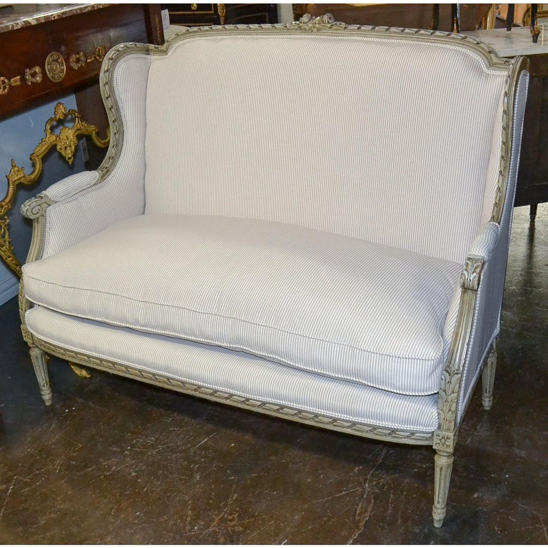 Exceptional 19th century French Louis XVI style sofa or settee with ivory painted patina. The crest hand-carved with rosebuds and leaf sprays. Beautifully contoured arms flow seamlessly to partially upholstered arms. The entire on Classic fluted and