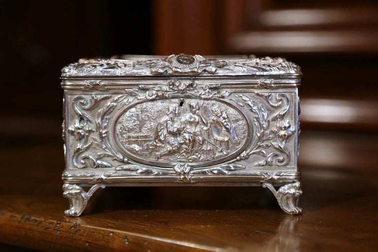 Place this elegant, antique silver coated copper box in your master bath to keep your jewelry safe and organized. Crafted in France, circa 1880, the ornate square casket sits on four scroll feet, and has four sides embossed with courting scenes. The