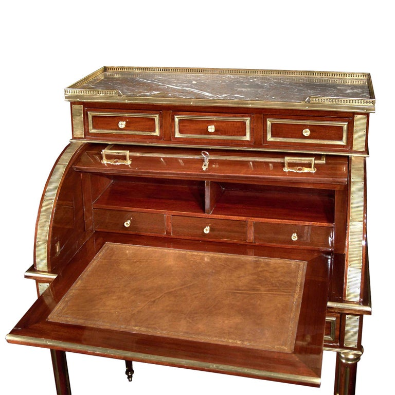 A very elegant 19th century French Louis XVI style mahogany, brass and ormolu-mounted ladies cylinder desk. The desk is raised by tapering fluted legs decorated by ormolu sabots and brass fitted filettes in the flutes. At the apron is a drawer below