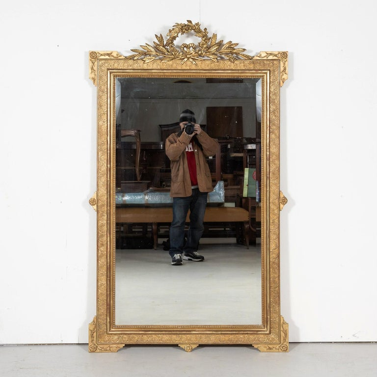 Ornate 19th century French Louis XVI style giltwood mirror, circa 1840s. This large, neoclassical mirror, having a richly carved giltwood frame, features typical elements of the Louis XVI period. The intricately carved and pierced crown depicts a
