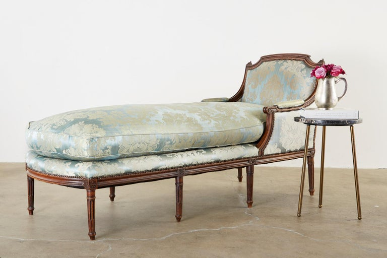 Gorgeous 19th century French chaise lounge or daybed made in the Louis XVI taste. Features a hand carved walnut frame with a flat back an arched crest rail. The arms gracefully curve down ending with scrolls and attach to a large seating area topped