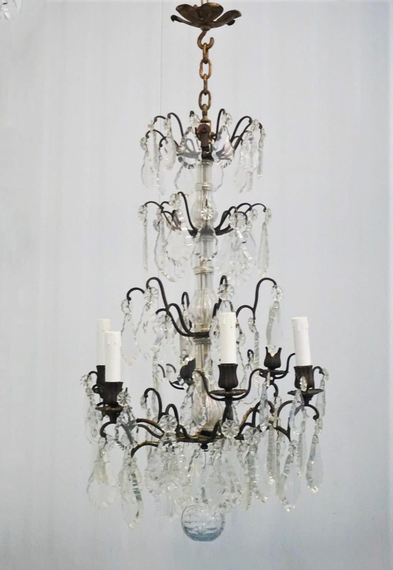 Wonderful antique Louis XVI style chandelier of rock crystal and old bronze, beautifully decorated with several tiers of large pendaloques in different shapes and sizes fixed with glass rosettes, finishing at the bottom with a large clear cut
