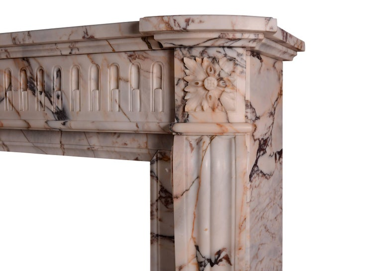 An unusually high French marble fireplace in the Louis XVI manner. The shaped jambs surmounted by carved square paterae, the bowed frieze with stop-flutes throughout. Shaped moulded shelf above. A veined marble from the Greek island of Skyros,
