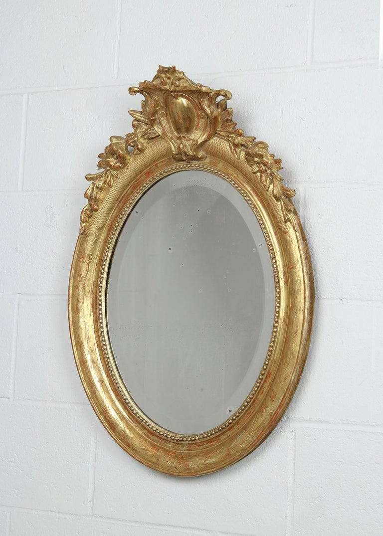 This circa 1840s French Louis XVI style gilt oval mirror is in good condition and has a carved frame with an intricated floral design crown. The mirror also has a water gilt finish. The mirror is fully reflective with minor wear from use and age.